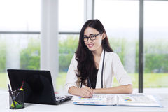 Pretty woman smiling at camera in office 1 Stock Photos