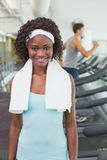 Pretty woman smiling at camera beside treadmills Royalty Free Stock Photos