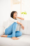 Pretty woman smiling on couch Royalty Free Stock Photo