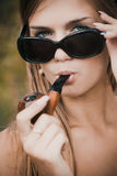 Pretty woman smoke tobacco-pipe Stock Image