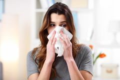 Pretty woman sneezing on tissue on couch in the living-room. Picture showing woman sneezing on tissue on couch in the living-room Stock Photo