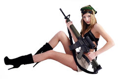 Pretty woman with sniper rifle. Beautiful sexy blond seats with sniper rifle over white background Royalty Free Stock Photography
