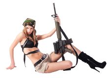 Pretty woman with sniper rifle on floor. Attractive sexy blond woman holding army rifle. Isolated over white Stock Photo