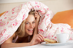 Pretty Woman Snuggled Under Duvet Eating Breakfast Stock Images