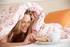 Pretty Woman Snuggled Under Duvet Eating Breakfast. Smiling Royalty Free Stock Images