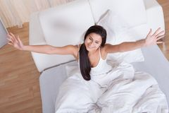 Pretty woman snuggling down in bed Stock Images