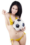 Pretty woman with a soccer ball isolated. Portrait of sexy woman wearing bikini holding a soccer ball pointing at camera Royalty Free Stock Photos