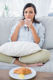 Pretty woman on sofa drinking coffee and having croissant Royalty Free Stock Image