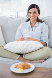 Pretty woman on sofa having coffee and croissant Royalty Free Stock Photo