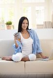 Pretty woman on sofa having tea using computer Stock Images