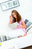 Pretty woman on sofa reading newspaper Stock Images
