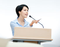 Pretty woman speaker at the podium Stock Images