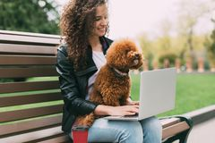 Pretty woman spending some time with her dog at park. Pretty woman spending time with her poodle dog at park and using laptop, copy space stock photography