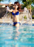 Pretty woman splashing in pool Royalty Free Stock Photography