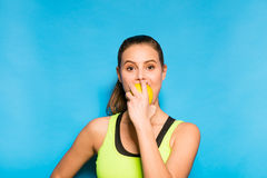 Pretty woman in sport equipment eating an apple in hand Royalty Free Stock Photos