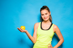 Pretty woman in sport equipment holding an apple in hand Royalty Free Stock Images