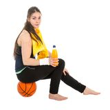 Pretty woman in sports wear sitting on basketball drinking juice Royalty Free Stock Photos