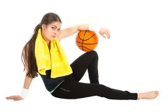 Pretty woman in sports wear sitting on floor with basketball, isolated on white Stock Photography