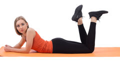 Pretty woman in sportswear lying training legs on a mat. Stock Photo