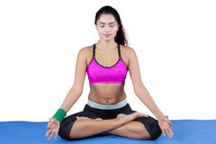 Pretty woman with sportswear meditating Stock Images