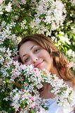 Pretty woman among a spring blossom Stock Images
