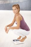 Pretty woman squat on scale Royalty Free Stock Images