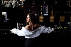 Pretty woman stand in bar look on light tonight. Beauty sexy woman in white fur coat stand near bar Royalty Free Stock Photography