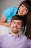 Pretty woman stand behind her boyfriend sitting on the couch Stock Photography