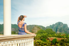 Pretty woman standing on the balcony watching beautiful mountain Royalty Free Stock Image
