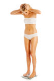 Pretty Woman Standing on Bathroom Scales. Royalty Free Stock Images