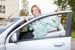Pretty woman standing behind car with opened door. Young pretty Caucasain woman standing behind a car with opened door Royalty Free Stock Images