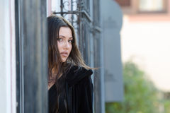 Pretty woman standing behind of a traditional window. With iron bars, horizontal photo Royalty Free Stock Image