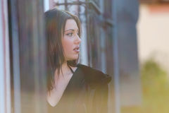 Pretty woman standing behind of a traditional window. With iron bars, horizontal photo Stock Images