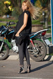 Pretty woman is standing near motorcycle Royalty Free Stock Photo