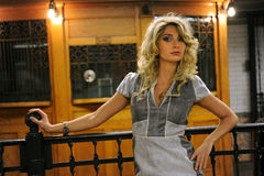 Pretty woman standing by old token booth Royalty Free Stock Photo