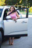 Pretty woman standing side of car with opened door Stock Image