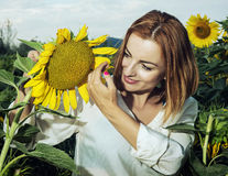 Pretty woman is standing by sunflower and look at it Stock Image