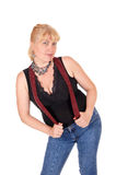 Pretty woman standing with suspenders. A woman in her forties standing in jeans and a black blouse with red Royalty Free Stock Photos