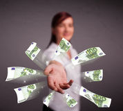 Pretty woman standing and throwing money Stock Images