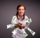Pretty woman standing and throwing money Stock Photography