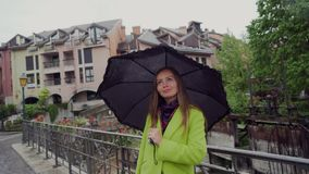 Pretty woman is standing under a black umbrella on the bridge in rainy day. Portrait. 4k stock video footage