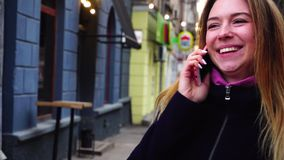 Adult woman talks by phone near restaurant. stock video footage