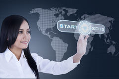Pretty woman with a start button. Young asian woman pressing a start button on a virtual screen to start new business in 2015 Stock Photo