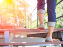 Pretty woman is stepping up a staircase. With Lens Flare or sunspot Royalty Free Stock Photo