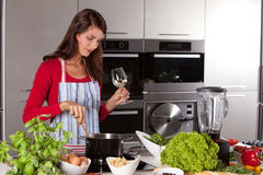 Pretty woman stirring in the pan. Attractive young female in the kitchen stirring in the pan while drinking wine Stock Photography