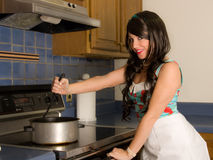 Pretty Woman Stirring Pot on Stove. A retro-inspired image of a beautiful young woman in a kitchen, stirring a large bowl of soup as she smiles at the viewer Royalty Free Stock Photography