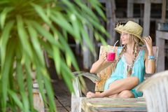 Pretty woman with straw hat sitting in the tropical shade. Drinking a fruit smoothie cocktail royalty free stock photos