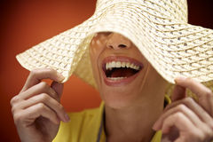 Pretty woman with straw hat smiling and having fun. Mid adult woman with straw hat smiling and having fun on red background Stock Images
