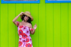 Pretty woman in a straw sunhat in Hawaii. Pretty woman in a straw sunhat and colorful red floral dress posing against a green wooden wall in Hawaii waving her Stock Photography