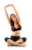 Pretty woman stretching. Young woman sitting on the floor and stretching Stock Image